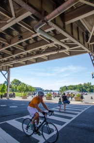 Vibrancy under the elevated Whitehurst Freeway in Georgetown (cyclists, pedestrians, vehicles on Water / K Street in foreground with the Georgetown Waterfront Park and Potomac River in background)